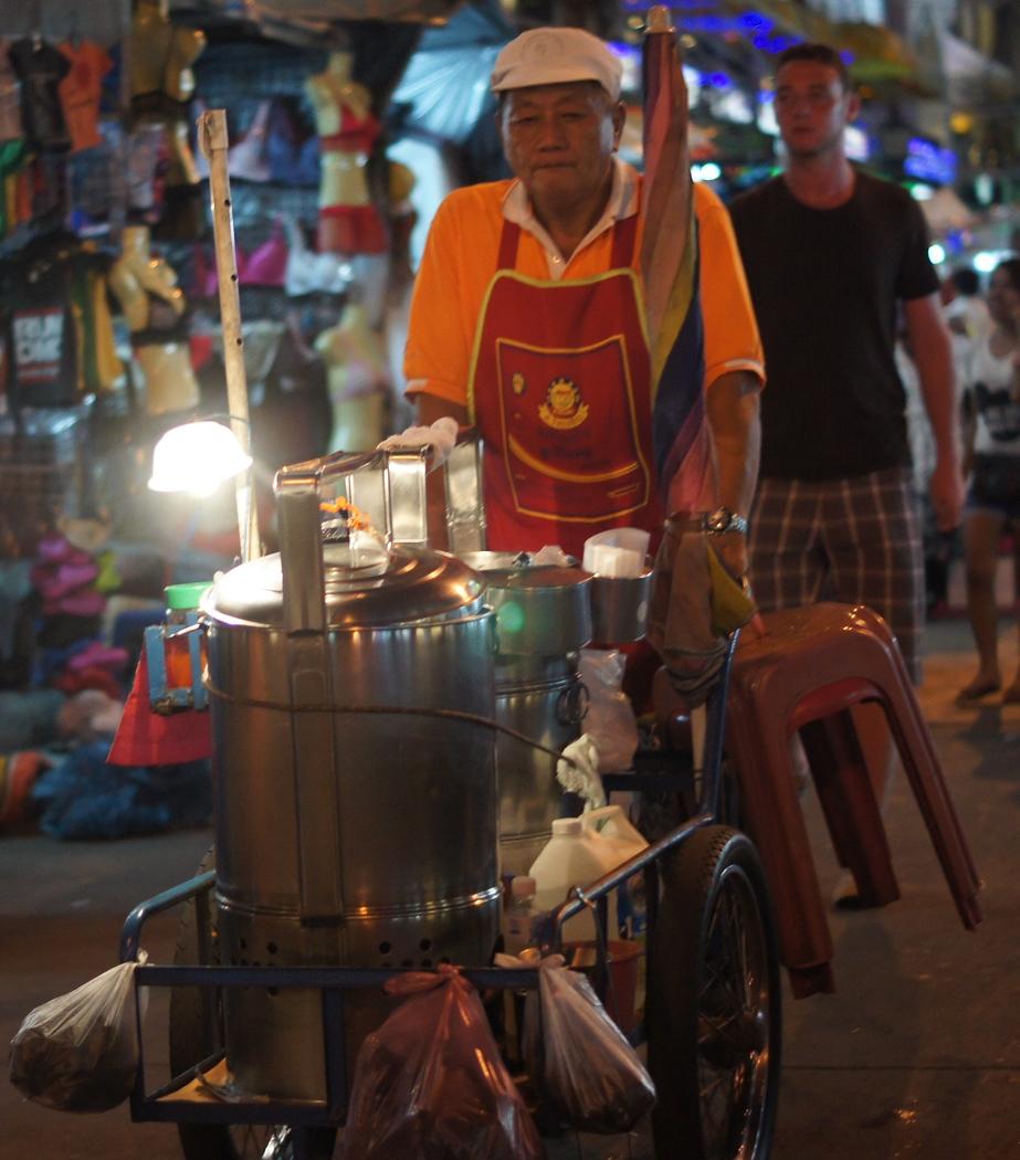 https://nomadicsamuel.com : A mobile street vendor pushes a cart down Khao San Road.