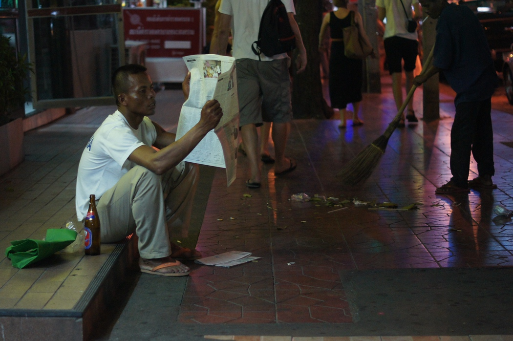 http://nomadicsamuel.com : Amidst all the chaos, this Thai man comfortably sits down on the curb to enjoy reading a newspaper and drink a beer.