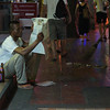 "<a href=""http://nomadicsamuel.com"">http://nomadicsamuel.com</a> : Amidst all the chaos, this Thai man comfortably sits down on the curb to enjoy reading a newspaper and drink a beer."