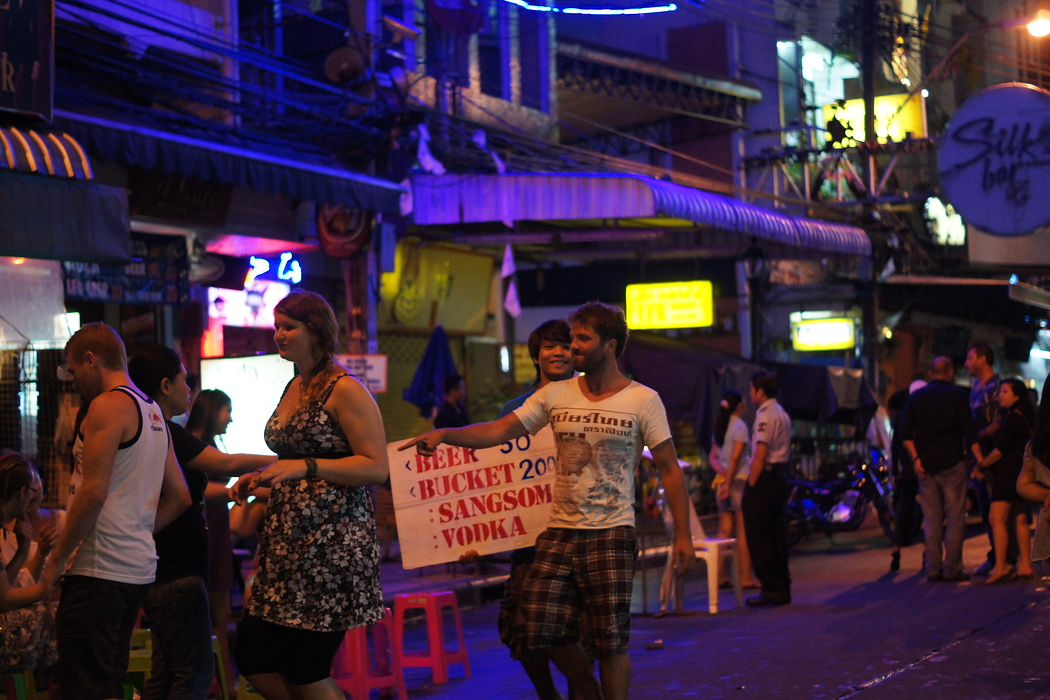 http://nomadicsamuel.com : A group of enthusiastic backpackers head to a street bar to sit down and drink buckets.