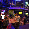 "<a href=""http://nomadicsamuel.com"">http://nomadicsamuel.com</a> : A group of enthusiastic backpackers head to a street bar to sit down and drink buckets."
