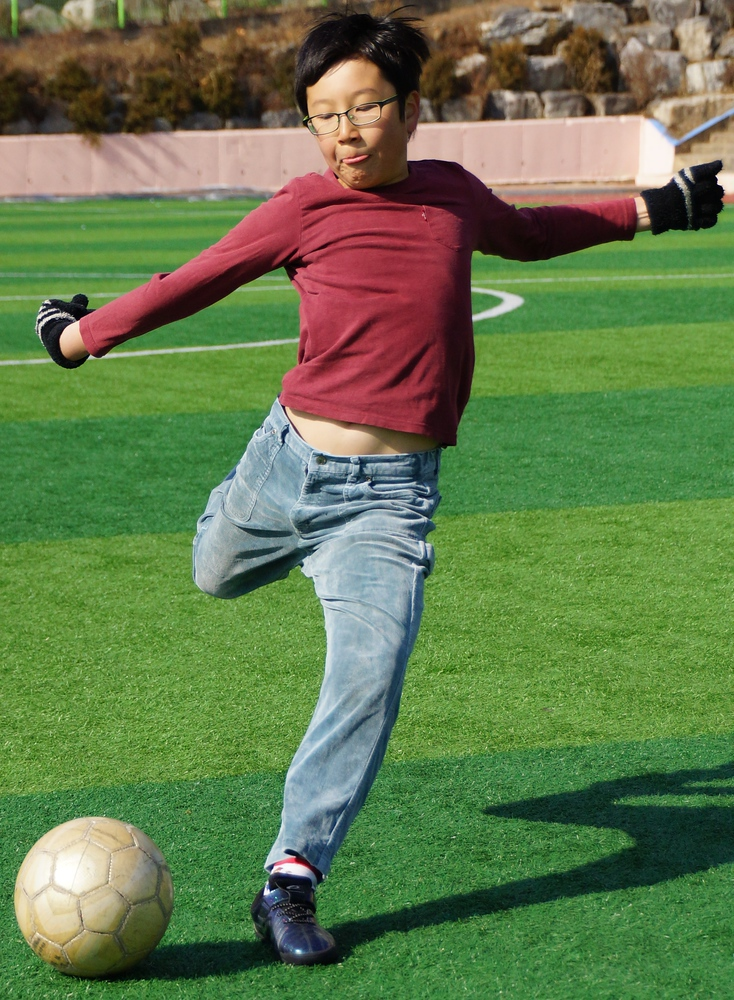 Another action shot of a boy just about to kick the football.