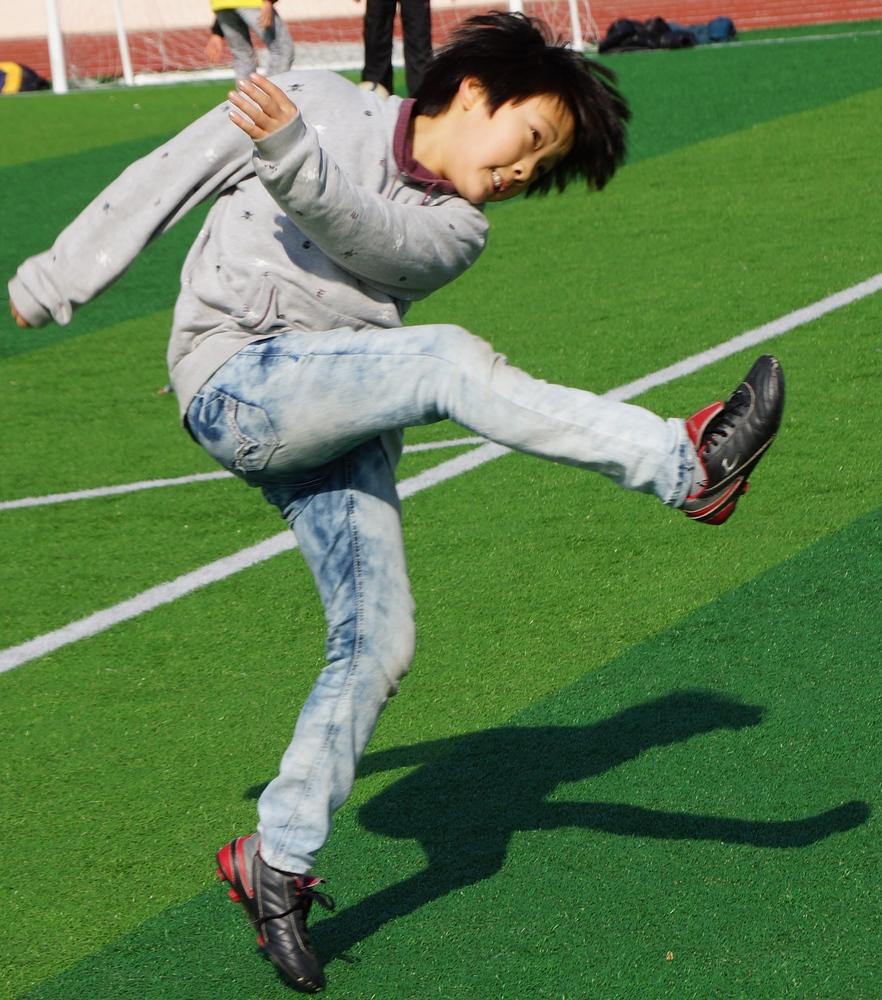 An action shot of a Korean boy kicking the ball.