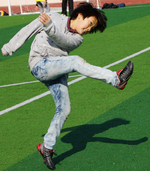 An action shot of a Korean boy kicking the ball.