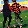 Two Korean boys compete for control over the soccer ball.
