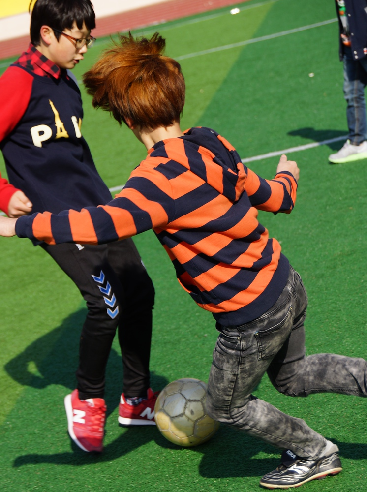 This is an action shot of the children kicking the ball around the school yard.