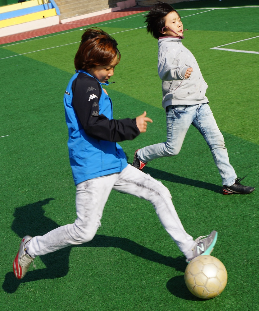 An action shot of a Korean student just about to kick the ball on net.