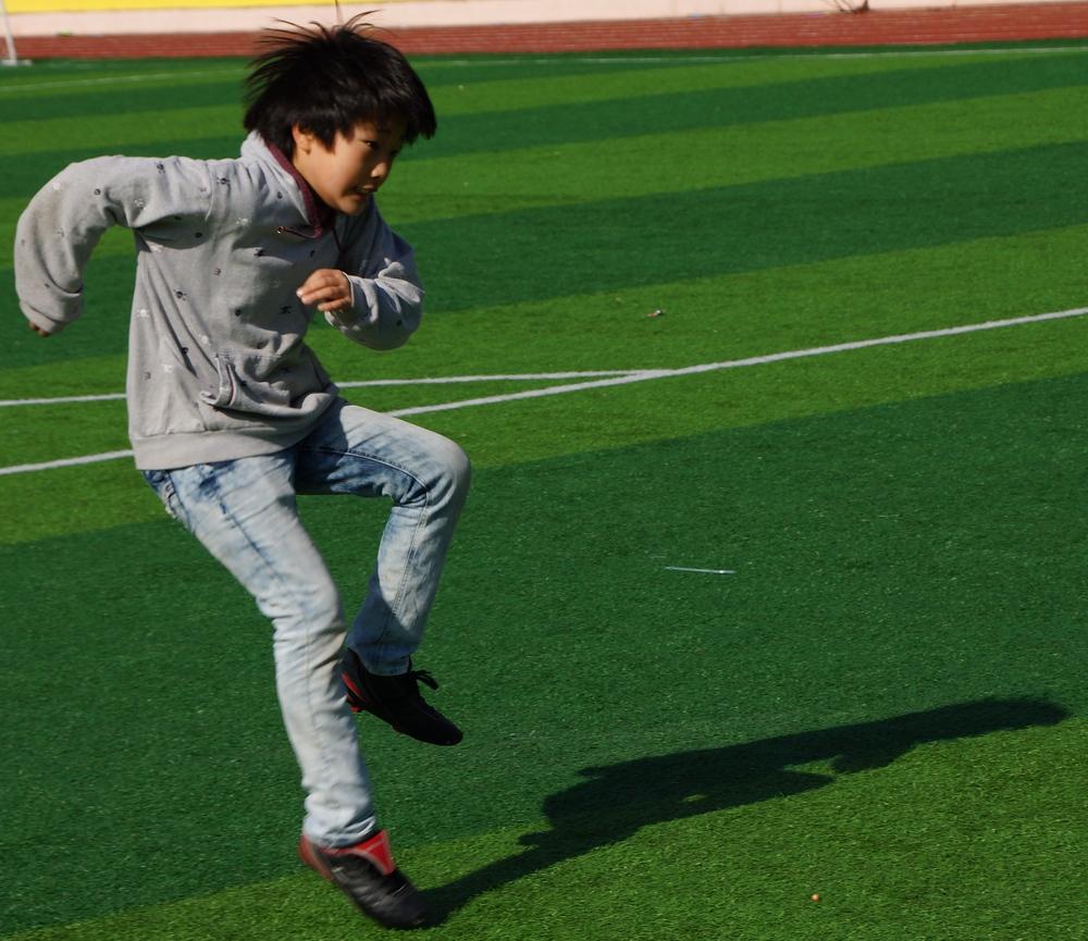 A Korean boy following through on a kick he had just made.