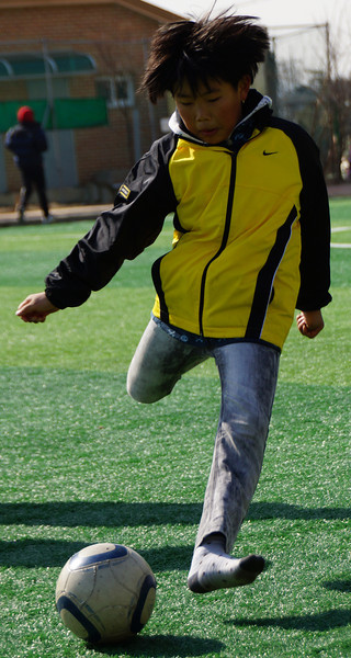A shot of a boy charging towards the ball just prior to striking it with his foot.