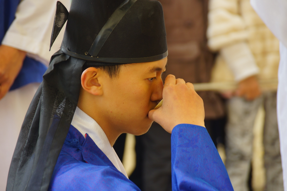 The Korean groom drinks from a cup during the wedding ceremony at the Korean Folk Village.