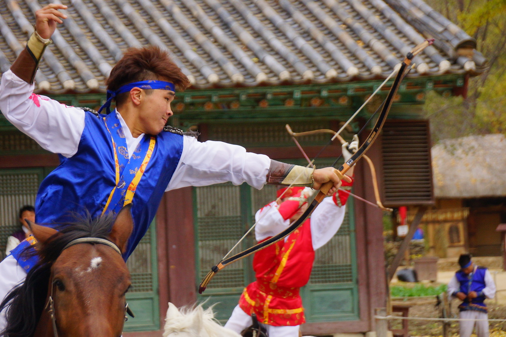 While riding the horses a select group of talented performers were shooting bows and arrows at the target in the centre of the ring.