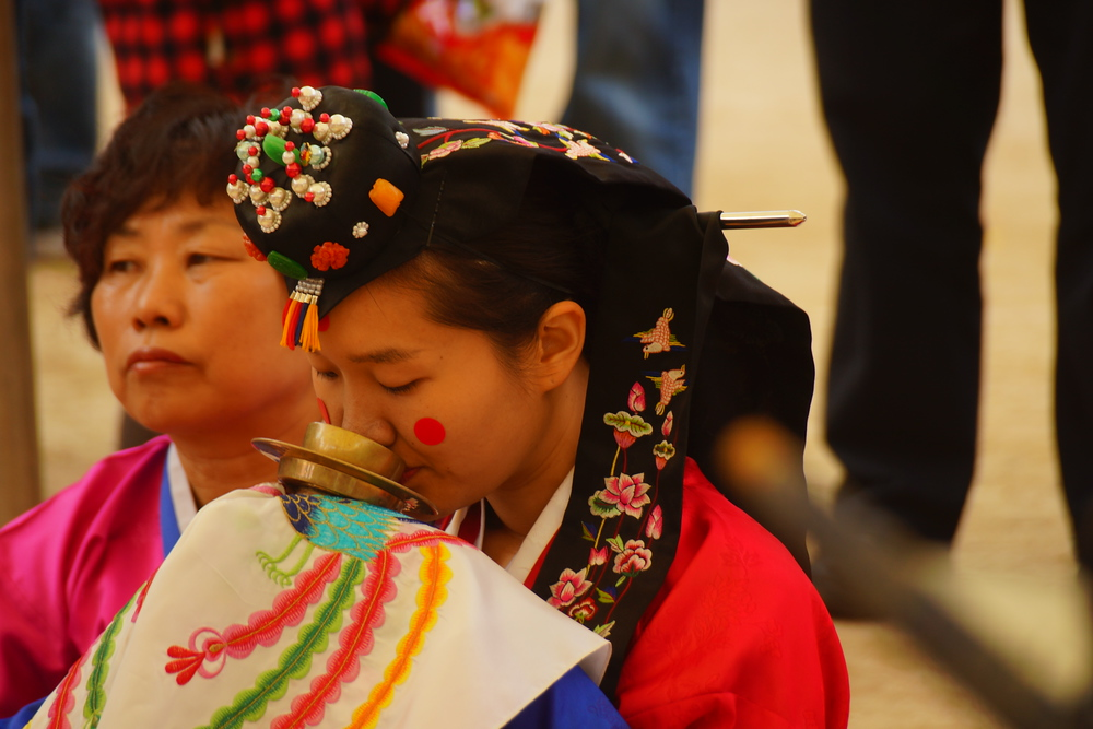 Here the Korean bride gracefully sips on the offering in her cup - Suwon, South Korea.