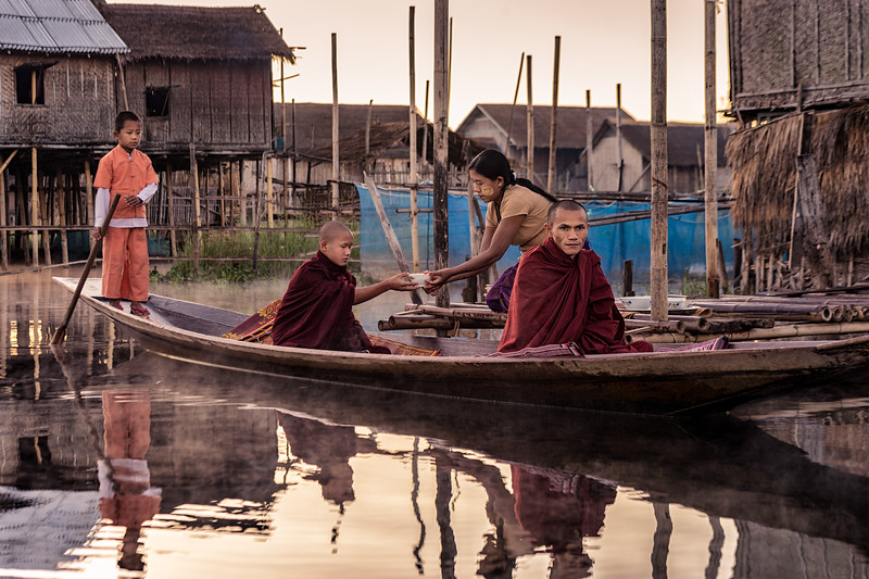Monks receive a food donation from a family at the floating village on Inle Lake.  Monasteries are heavily dependent on donations from the monks' families and nearby villages.