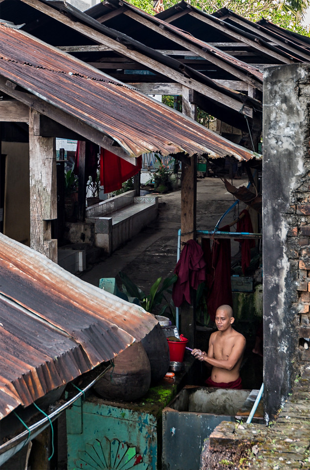 Monk bathes outside his quarters, adjacent to Chaukhtatgyi Temple in Yangon, Myanmar
