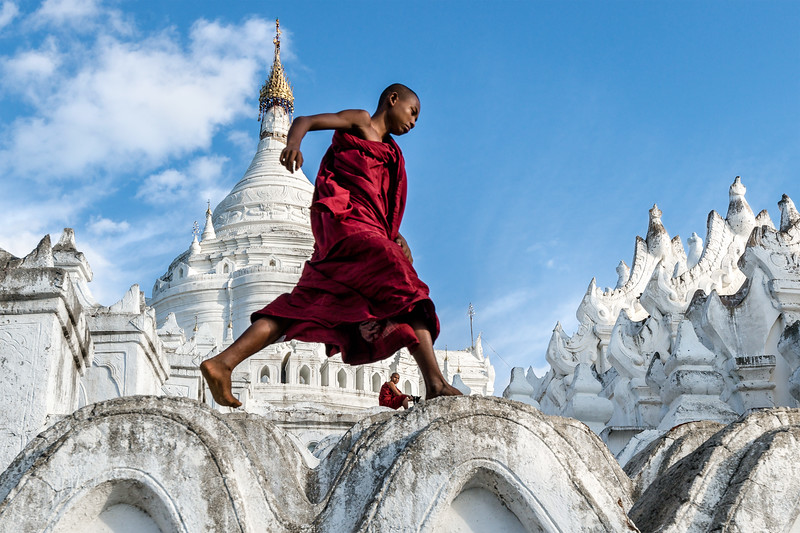 Monk leaps across the structure of Hsinbyume Pagoda in Mingun while his friend plays with a dog in the background.