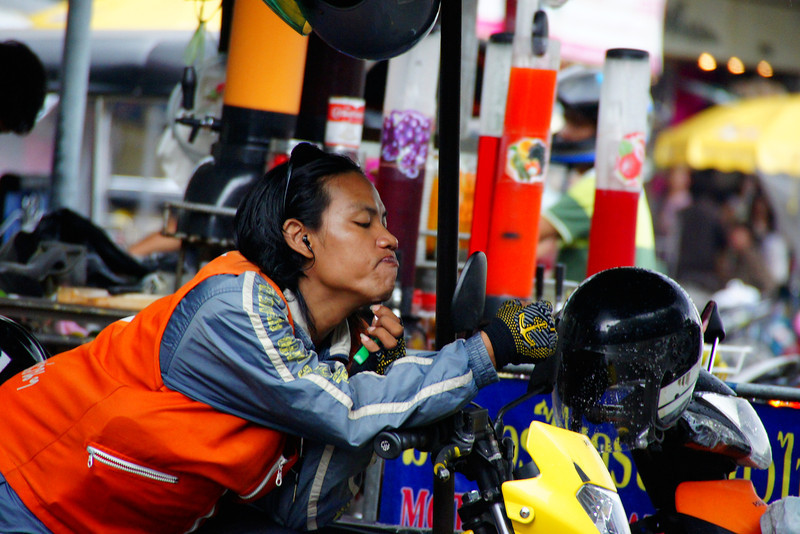 A Thai man shaves while listening to his mp3 player on his motorbike - Bangkok, Thailand.