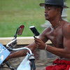 A Khmer man attempts to ride his bicycle while looking into a mirror and shave - Battambang, Cambodia.