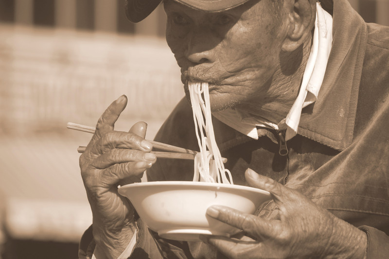 A Vietnamese man slurping noodles into his mouth.