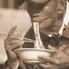 A Vietnamese man slurping noodles into his mouth.