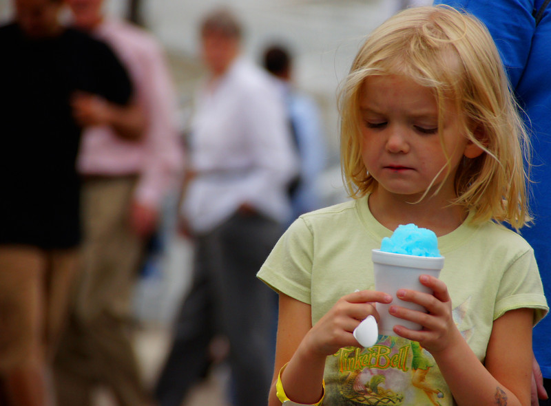 A girl looks down at her blue shaved ice with a local of disappointment.  Maybe Mom got her the wrong flavour :P