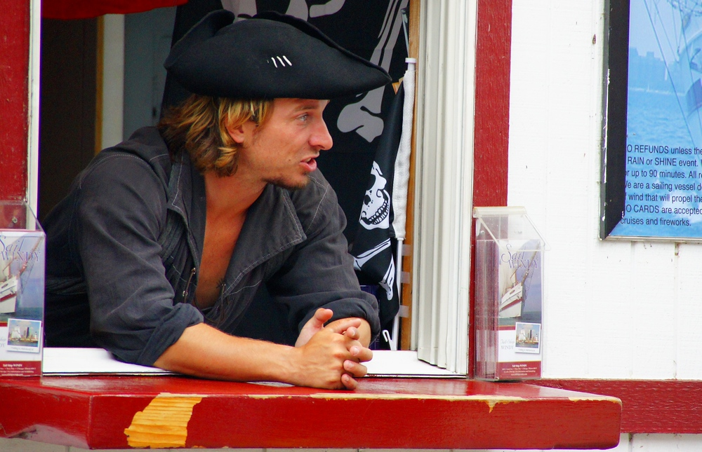 A vendor wearing a sailing/pirate hat and uniform tries to persuade passer-bys to take a tour.