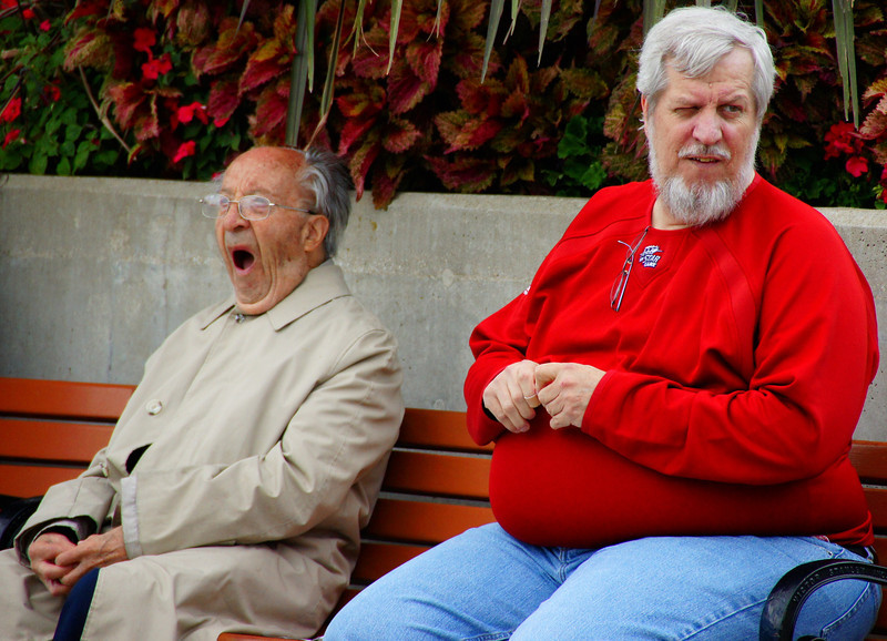 An elderly man wearing a trench coat yawns while another distinct face winks.