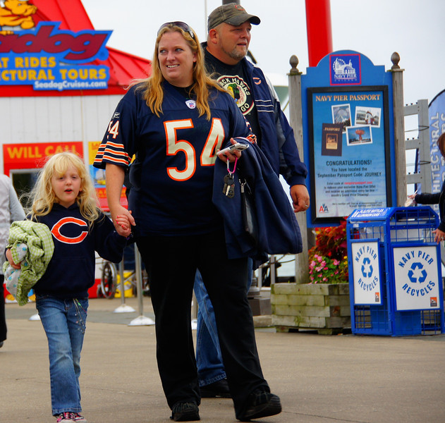 A family decked out entirely in Chicago Professional Sports Team attire (Blackhawks and Bears) wander the Pier.