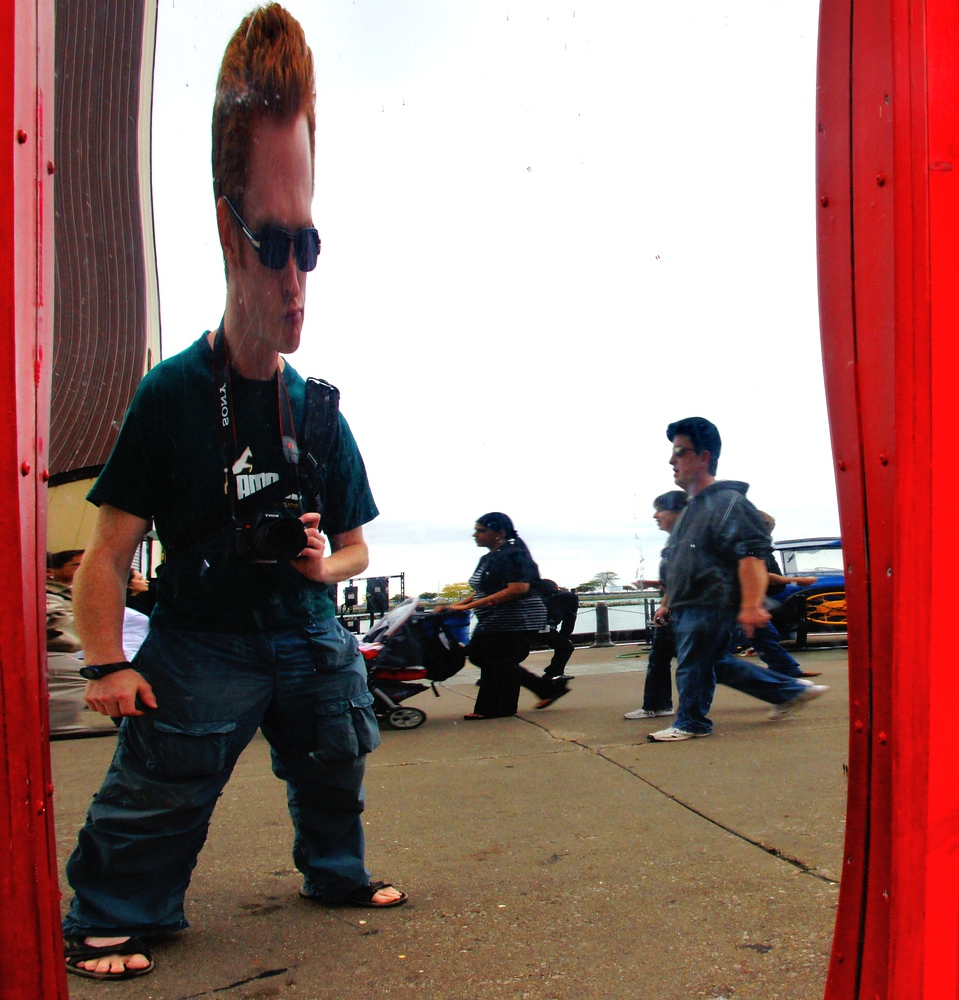 A goofy but somewhat familiar looking tourist takes a strange portrait of himself via a distorted mirror.