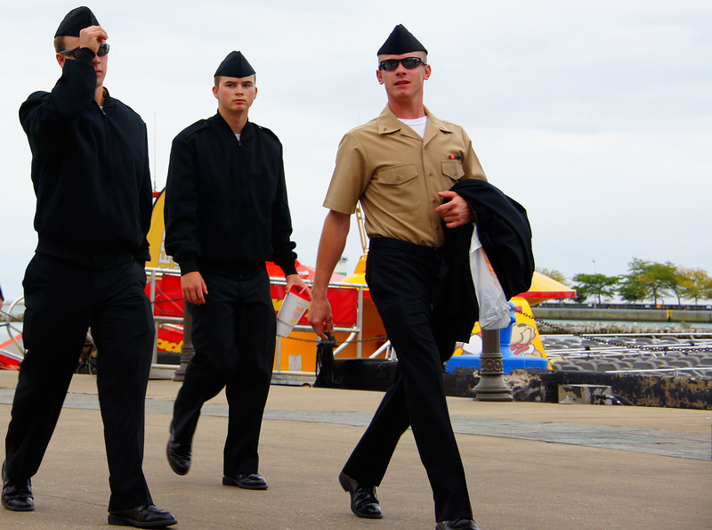 A group of young Navy American men confidently strut around.