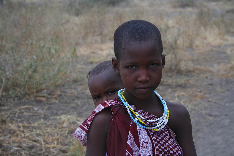 """A young Masai girl with a baby on her back at Lake Manyara: <br /> <a href=""""http://nomadicsamuel.com/photo-essays/the-people-of-tanzania"""">http://nomadicsamuel.com/photo-essays/the-people-of-tanzania</a>"""