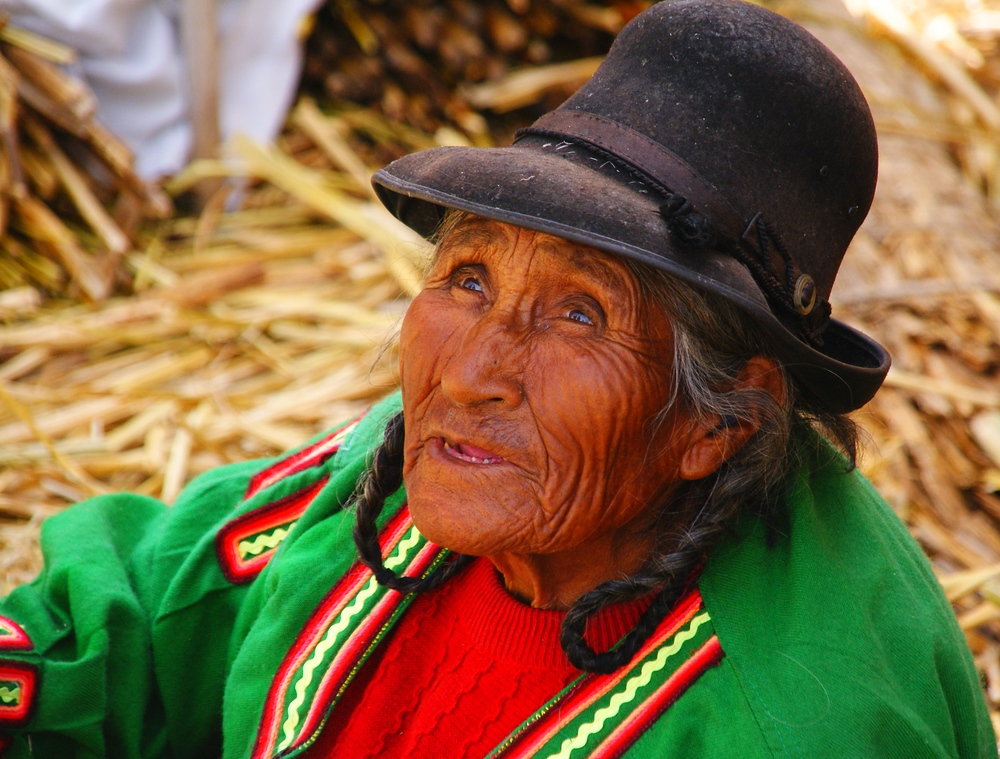 An elderly lady with leathery skin and wrinkles wearing a bowler hat and colourful attire.