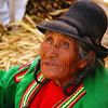 "An elderly lady with leathery skin and wrinkles wearing a bowler hat and colourful attire:<br /> <a href=""http://nomadicsamuel.com/photo-essays/lake-titicaca-uros-puno-peru"">http://nomadicsamuel.com/photo-essays/lake-titicaca-uros-puno-peru</a>"