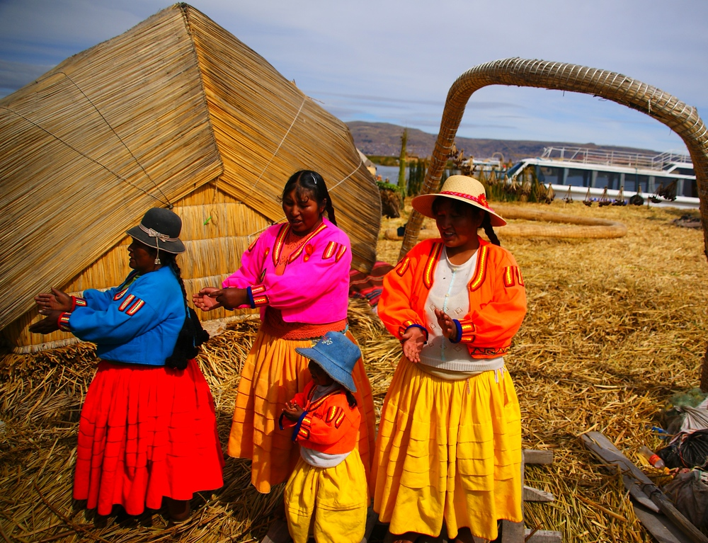 A group of gregarious Uros ladies decked out in traditional attire perform songs and dance for a group of foreign tourists.