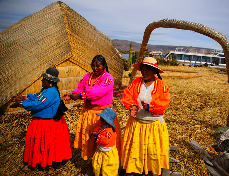 "A group of gregarious Uros ladies decked out in traditional attire perform songs and dance for a group of foreign tourists:  <a href=""http://nomadicsamuel.com/photo-essays/lake-titicaca-uros-puno-peru"">http://nomadicsamuel.com/photo-essays/lake-titicaca-uros-puno-peru</a>"