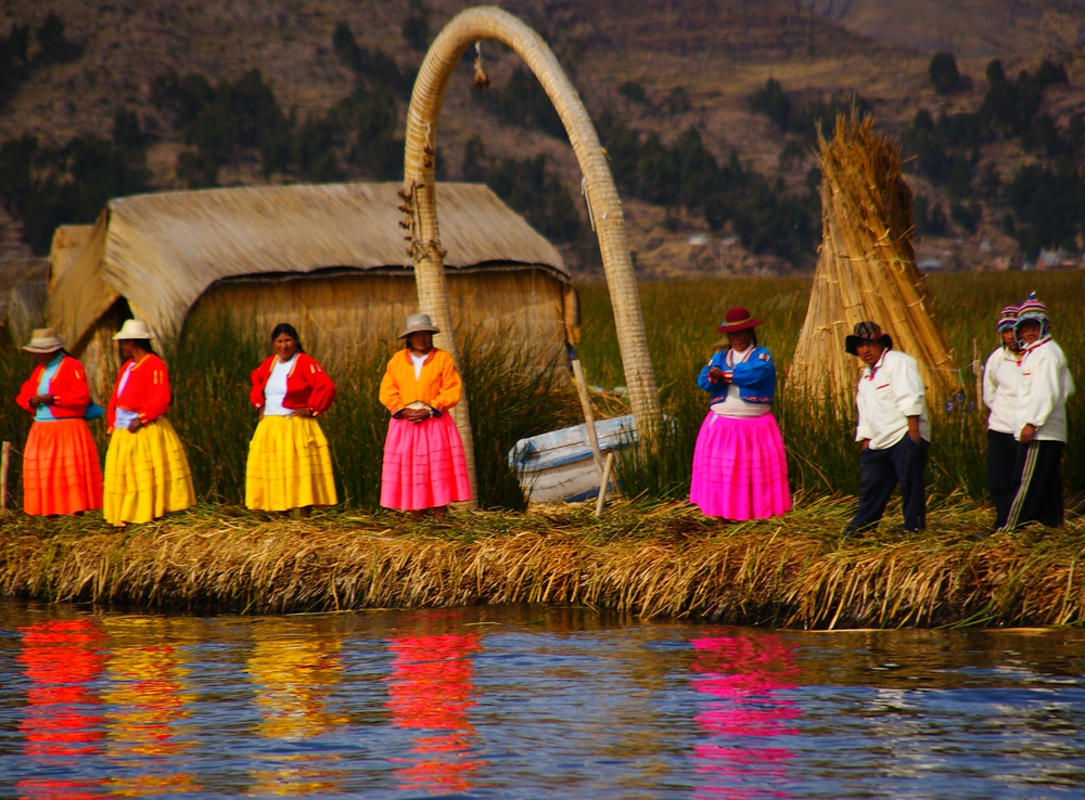 The colourful ladies of the Uros people, whose attire is reflected in the water, waiting to greet our tour boat - Lake Tititcaca, Peru.