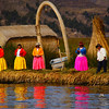 "The colourful ladies of the Uros people, whose attire is reflected in the water, waiting to greet our tour boat - Lake Tititcaca, Peru:  <a href=""http://nomadicsamuel.com/photo-essays/lake-titicaca-uros-puno-peru"">http://nomadicsamuel.com/photo-essays/lake-titicaca-uros-puno-peru</a>"