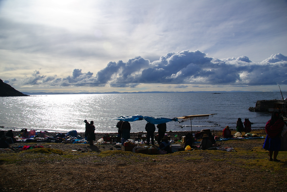 A wide angle shot of locals setting up their stalls overlooking pristine Lake Titicaca.
