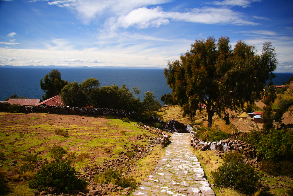 A scenic path leading down to small houses overlooking Lake Titicaca.