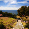 "A scenic path leading down to small houses overlooking Lake Titicaca:  <a href=""http://nomadicsamuel.com/photo-essays/lake-titicaca-uros-puno-peru"">http://nomadicsamuel.com/photo-essays/lake-titicaca-uros-puno-peru</a>"