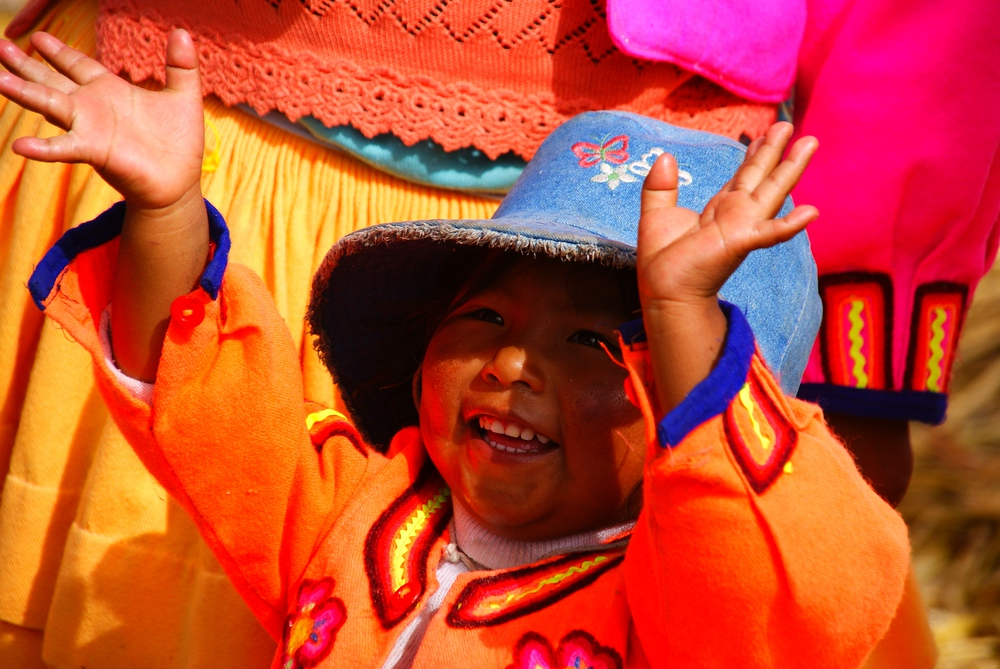 A young child dressed in traditional colourful clothes gleefully sings and performs for a group of tourists - Lake Titicaca, Peru.