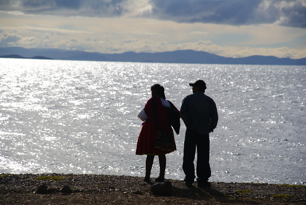 A couple look out over Lake Titicaca in the late afternoon - Peru.