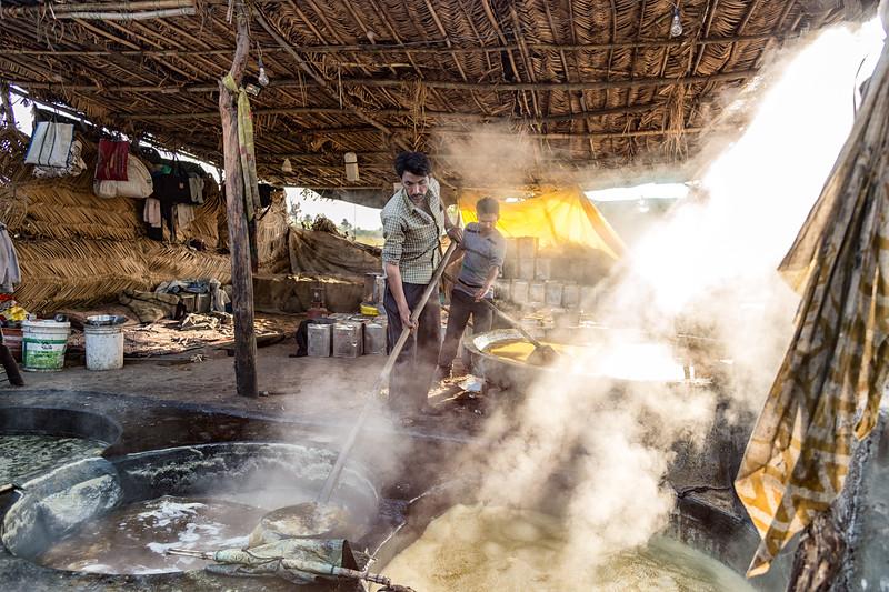 Two men working vats of sugar cane juice at a farm near Bundi, India