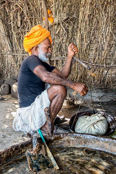 Sugar farmer verifies that the fresh bag of sugar weighs 5kg