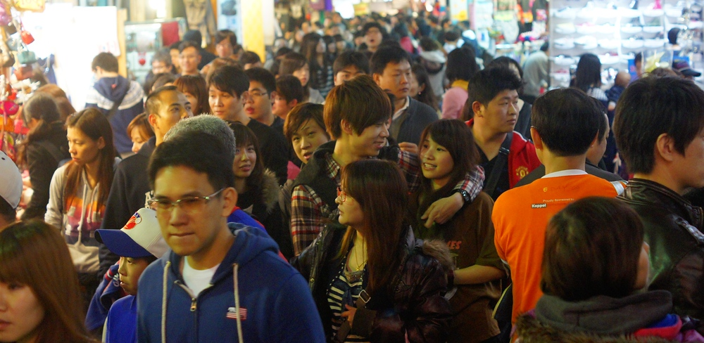 A couple embraces with a hug as they wander the along the crowded Shilin Night Market.