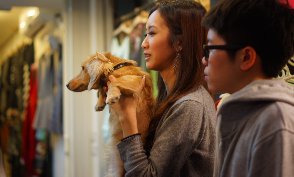 A Taiwanese lady holding her dog smiles in this photo.
