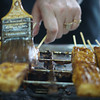 A vendor brushes the stinky tofu (臭豆腐) that lays skewered on the grill.