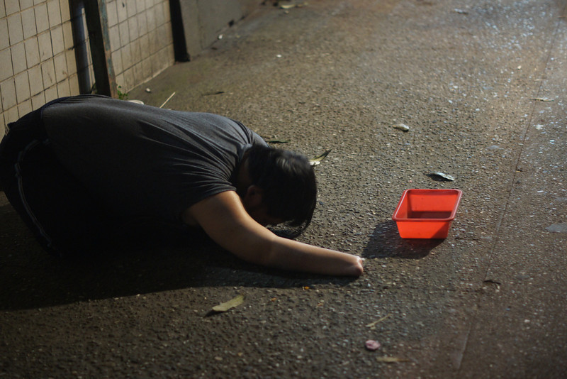 A homeless Taiwanese man extends his arm out for donations in a dimly lit section just outside the market.