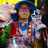 A young Taiwanese vendor dressed in funky attire tries to peddle shoes on the curb.