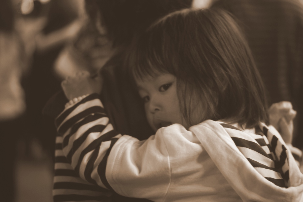 A child holds onto her mothers back as she is being carried around the market.