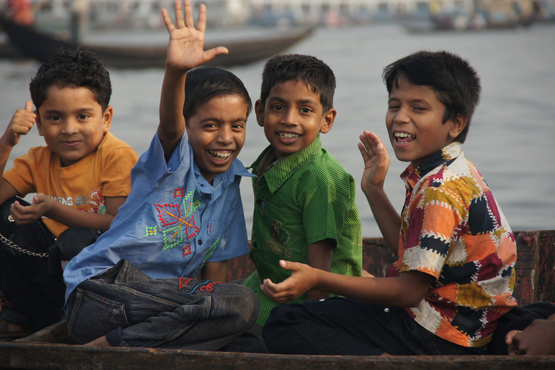 A trip along the Sadarghat (Buriganga River) by simple row boat was definitely the highlight of my trip in Bangladesh.  In this photo these group of boys smile and wave to me as I'm passing by.